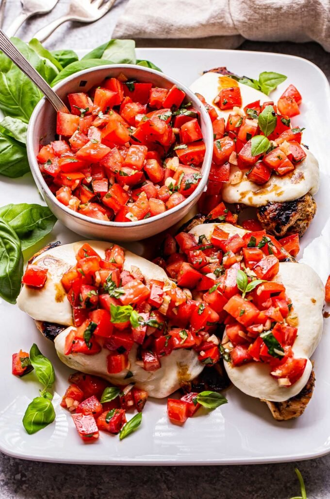 white serving plate with grilled chicken breasts topped with melted mozzarella and tomato basil topping.