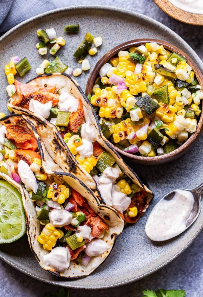 Two Grilled Salmon Tacos with Corn Salsa on a gray plate with a wooden bowl of the salsa on the plate and a spoon with the chipotle crema on it.