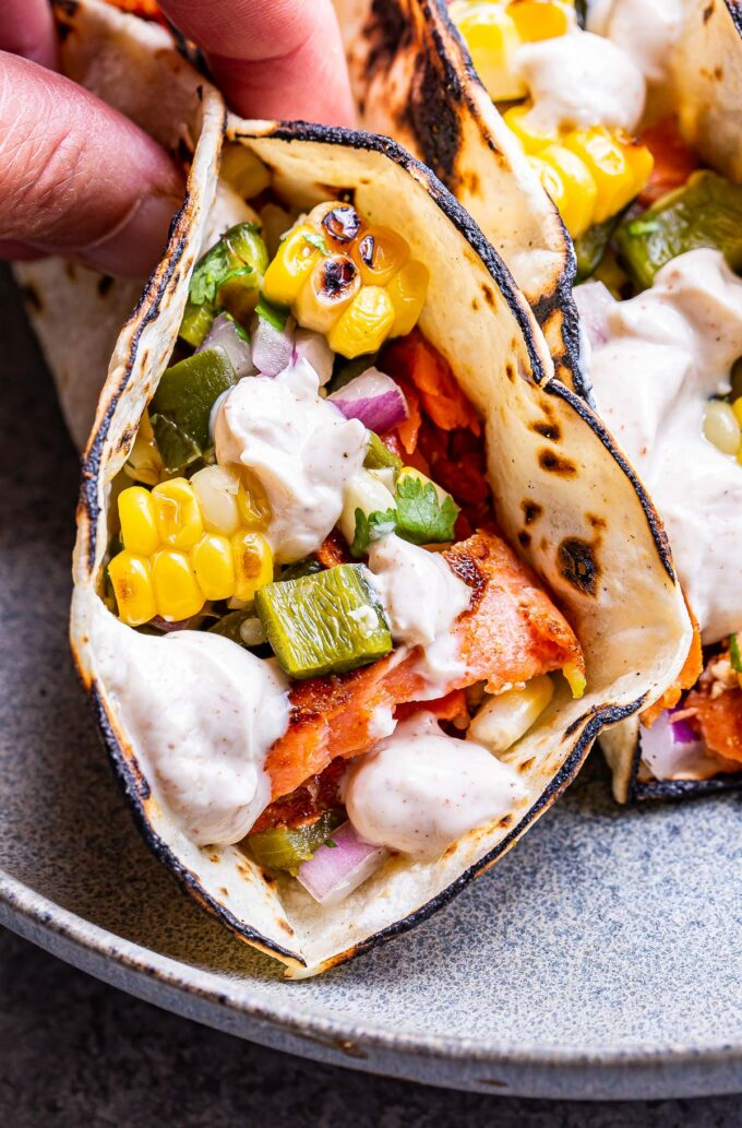 Hand picking up one of the Grilled Salmon Tacos with Corn Salsa