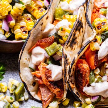 Two Grilled Salmon Tacos with Corn Salsa on a gray plate with a wooden bowl of corn salsa on the plate.