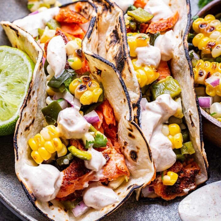 Two Grilled Salmon Tacos with Corn Salsa on a gray plate.