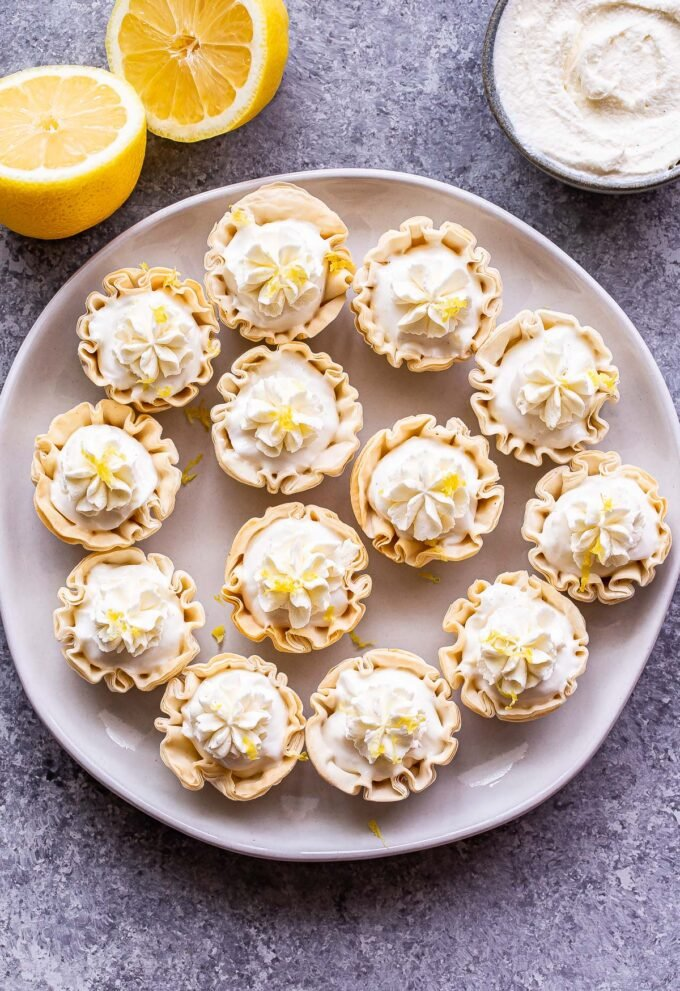 Mini Lemon Cream Pies topped with whipped cream on a white plate. A lemon cut in half and a bowl of whipped cream are behind the plate.