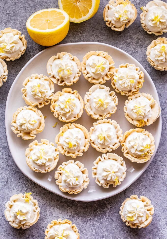 Mini Lemon Cream Pies in phyllo shells topped with whipped cream on a white plate. More pies are surrounding the plate.