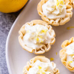 Several Mini Lemon Cream Pies in phyllo shells on a white plate.