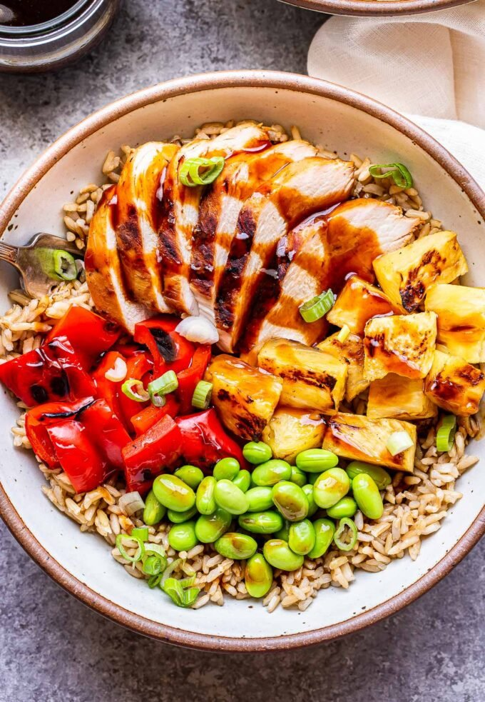 White bowl filled with teriyaki chicken, pineapple, red pepper, edamame and brown rice.