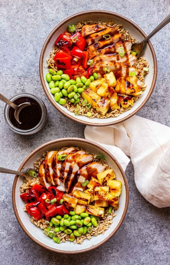 two white bowls with forks in them. Bowls are filled with teriyaki chicken, pineapple, edamame, red bell pepper and rice.