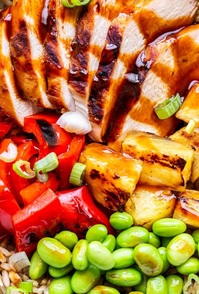 Closeup photo of teriyaki chicken, pineapple, red pepper, and edamame drizzled with teriyaki sauce.