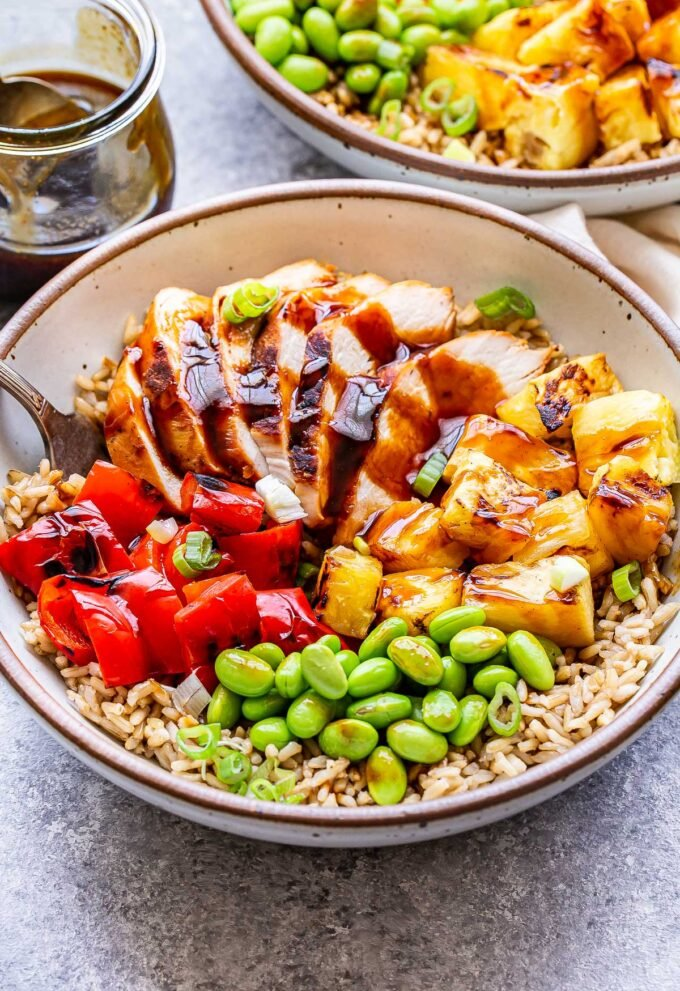 White bowl filled with brown rice, edamame and grilled pineapple, chicken and red pepper. Topped with teriyaki sauce. A second bowl and a jar of the sauce are behind it.
