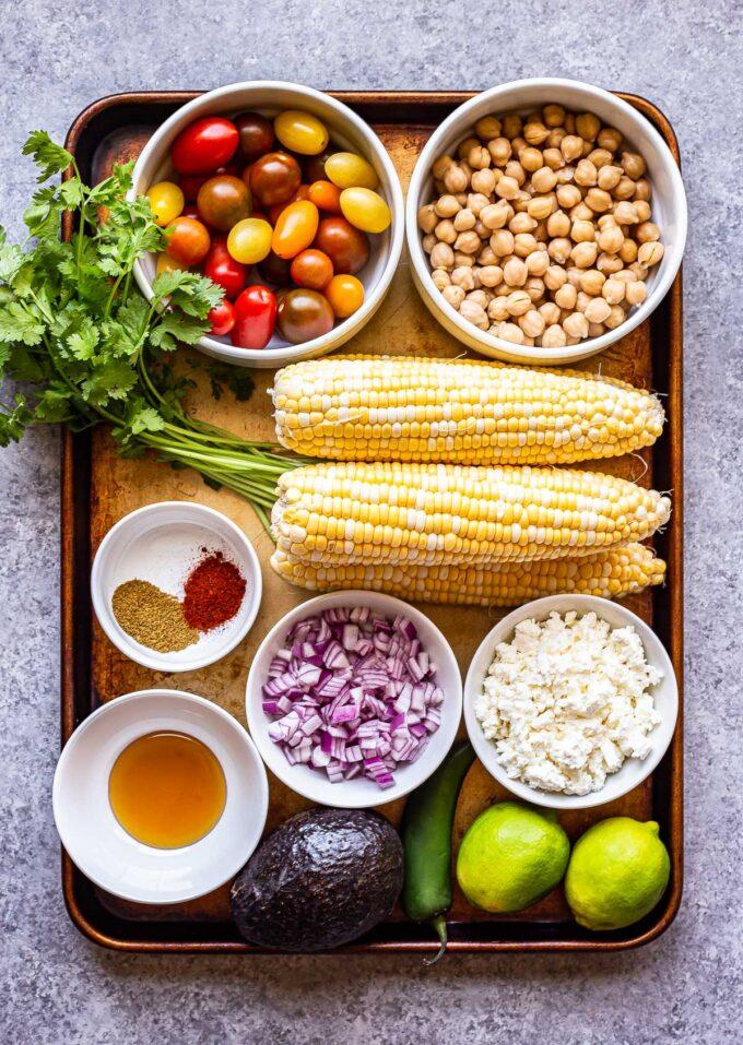 ingredients used to make Tomato Avocado Corn Salad on a sheet pan.