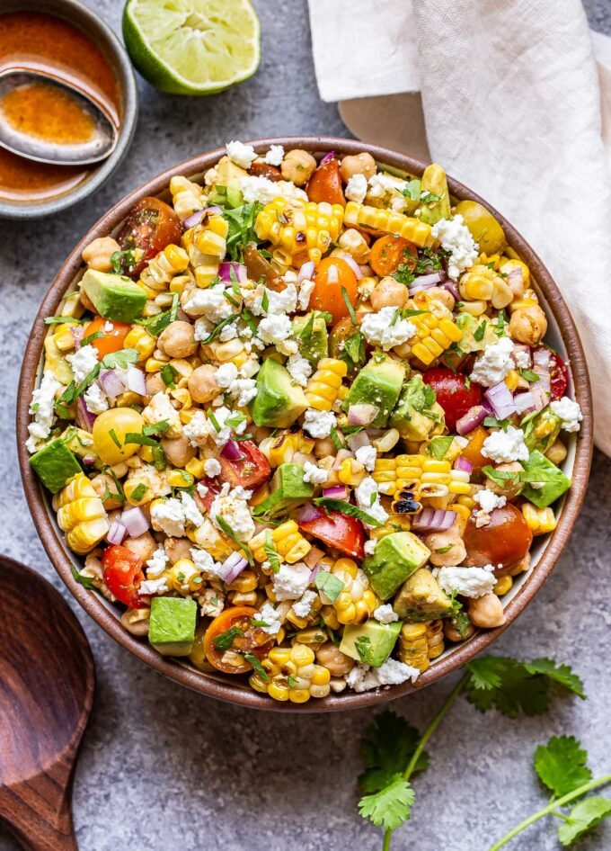 Tomato Avocado Corn Salad with chickpeas and feta in a white bowl. A bowl of vinaigrette behind the salad.