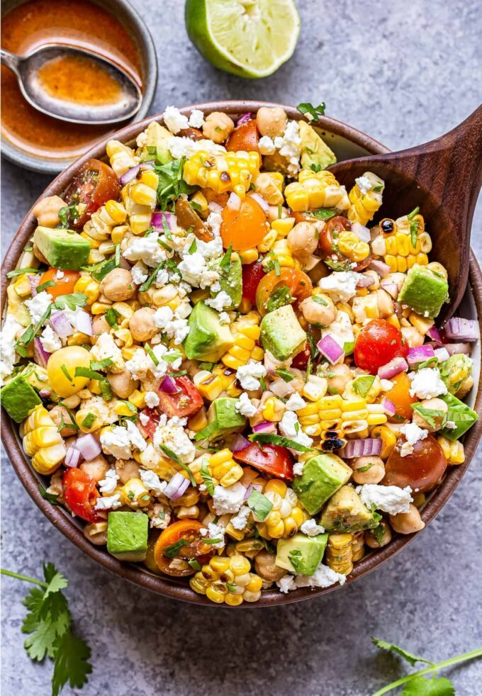 Tomato Avocado Corn Salad in white serving bowl with a wooden spoon in it. A bowl of vinaigrette and half of a lime are behind the salad bowl.
