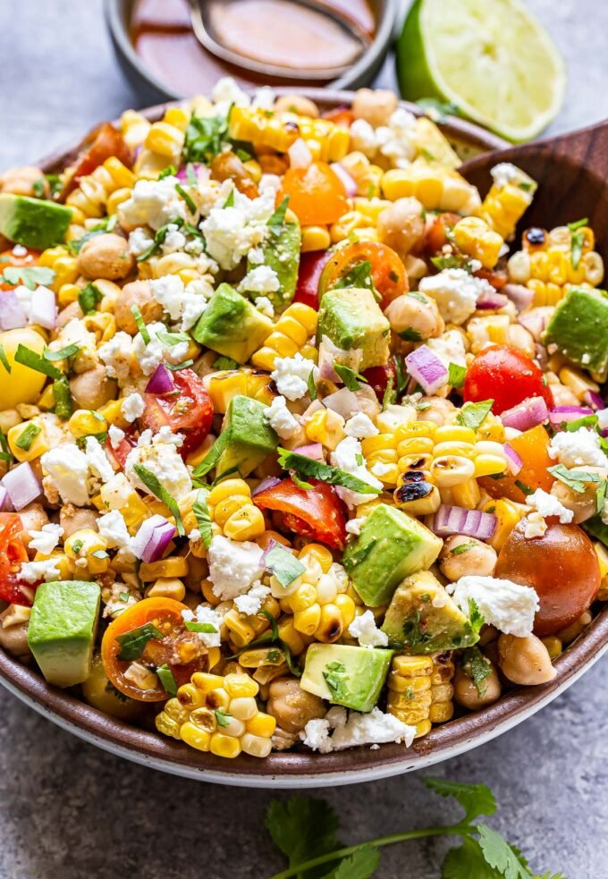 Tomato Avocado Corn Salad in a serving bowl with a wooden spoon in it.