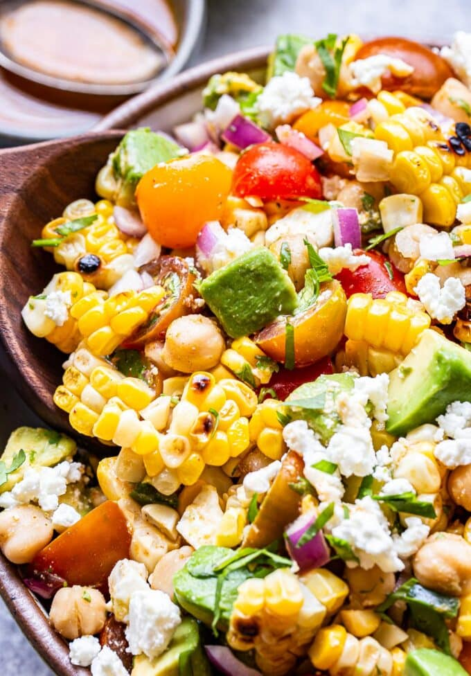 wooden spoon scooping up some of the Tomato Avocado Corn Salad.