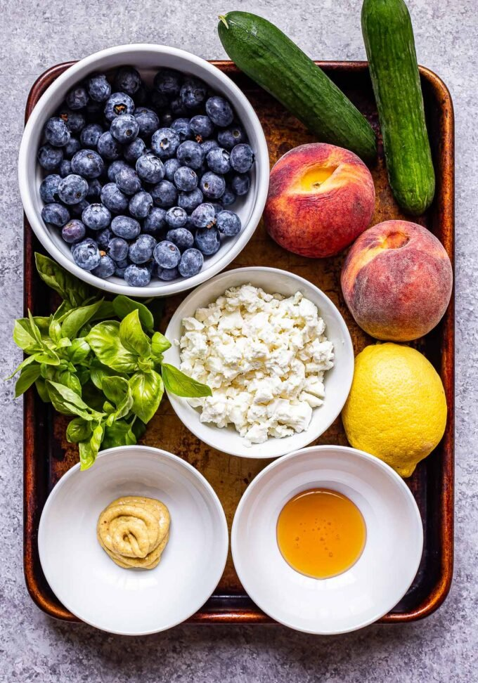 Ingredients used to make blueberry peach feta salad on a sheet pan.
