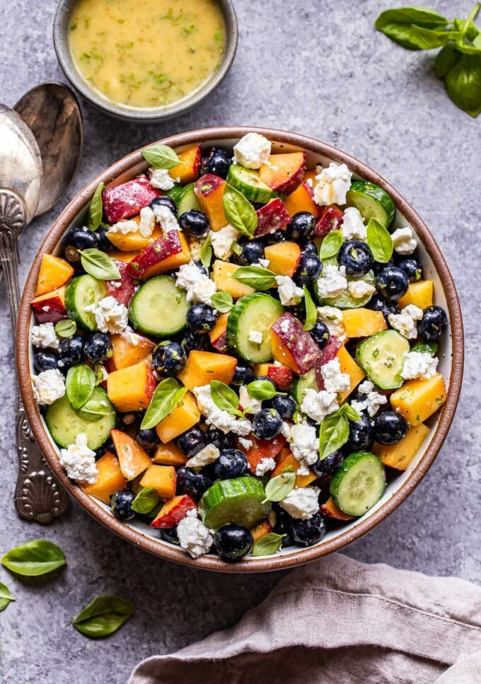 Blueberry Peach Feta Salad with cucumbers in a white serving bowl. Serving spoons are next to the salad and a bowl of the vinaigrette is behind it.