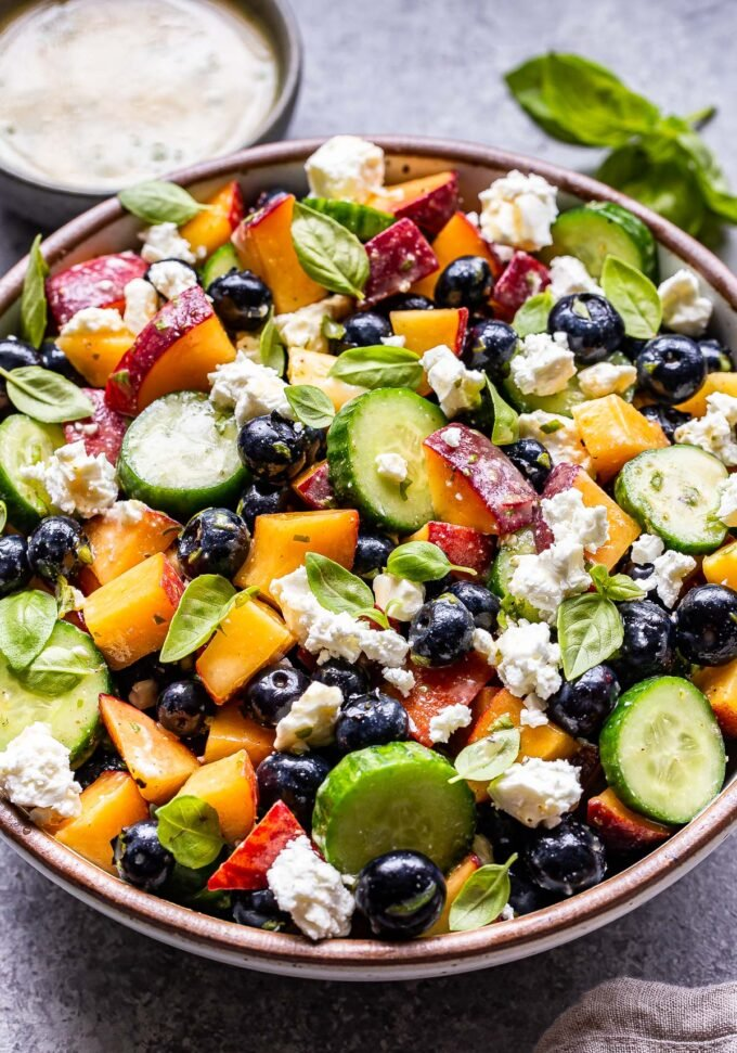 Blueberry Peach Feta Salad with cucumbers in a white serving bowl with a bowl of lemon basil dressing behind it.