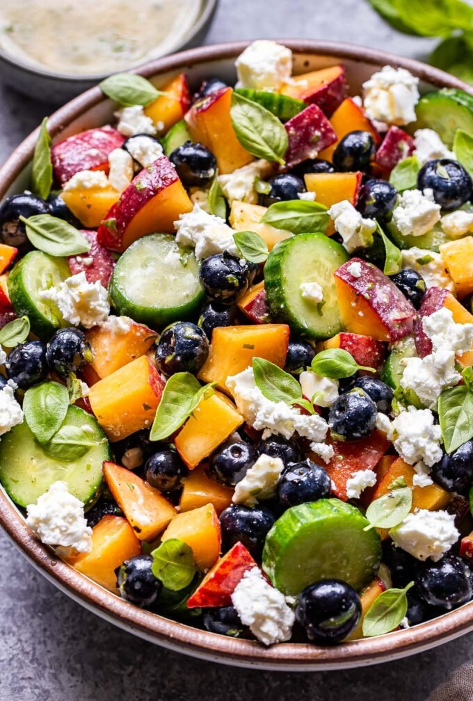 Blueberry Peach Feta Salad with cucumbers in a white serving bowl.