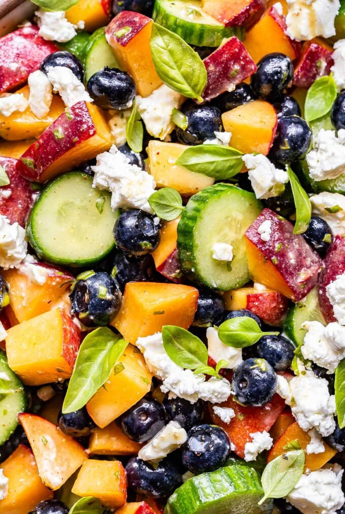 closeup photo of Blueberry Peach Feta Salad with cucumbers and basil.