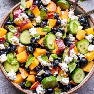 Blueberry Peach Feta Salad in a white serving bowl with two spoons and a bowl of the vinaigrette behind it.