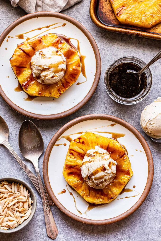 two white plates with slices of Grilled Pineapple with vanilla ice cream and Rum Sauce on them. A jar of rum sauce and two spoons are next to the plates.