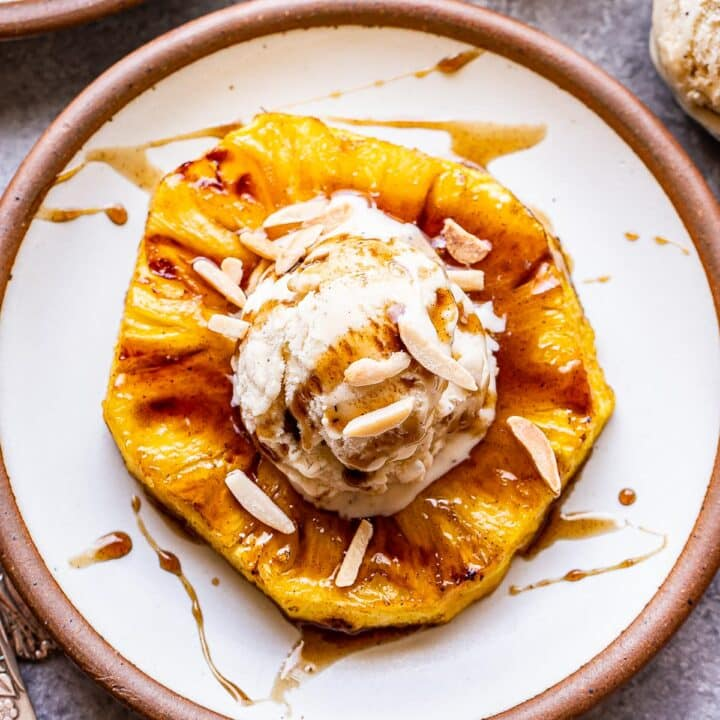 A white plate with a grilled pineapple ring topped with vanilla ice cream and rum sauce.