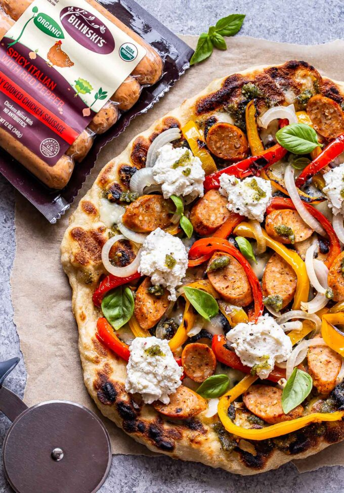 Overhead photo of Grilled Sausage and Peppers Pizza on a piece of parchment paper with a package of Bilinski's chicken sausage and a pizza cutter next to it.