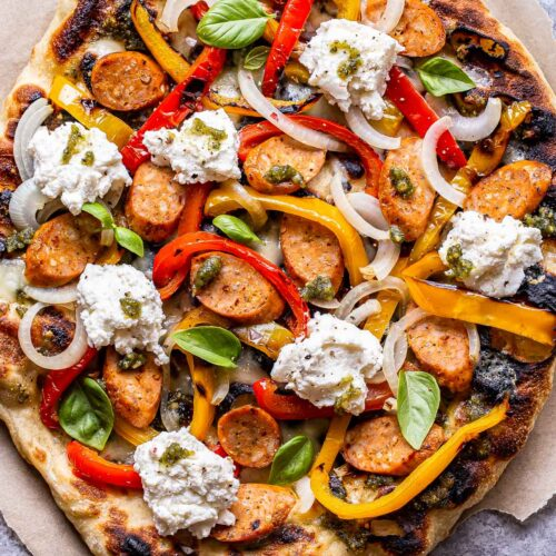 Overhead photo of Grilled Sausage and Peppers Pizza on a piece of parchment paper.