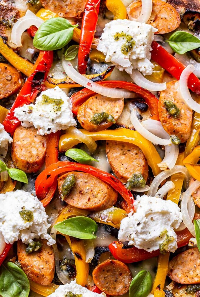 closeup photo of Grilled Sausage and Peppers Pizza with pesto, ricotta, and onions.