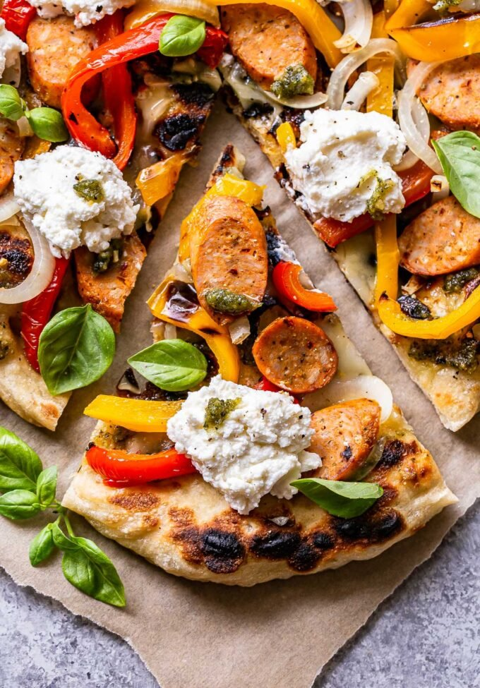 A slice of the Grilled Sausage and Peppers Pizza topped with ricotta cheese