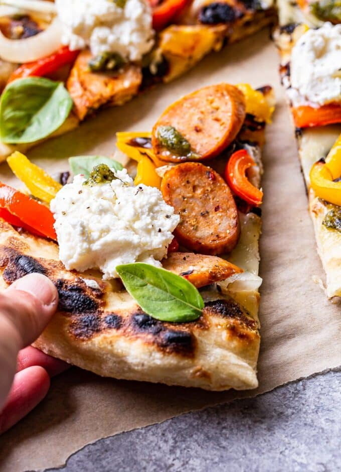 Hand grabbing a slice of the Grilled Sausage and Peppers Pizza