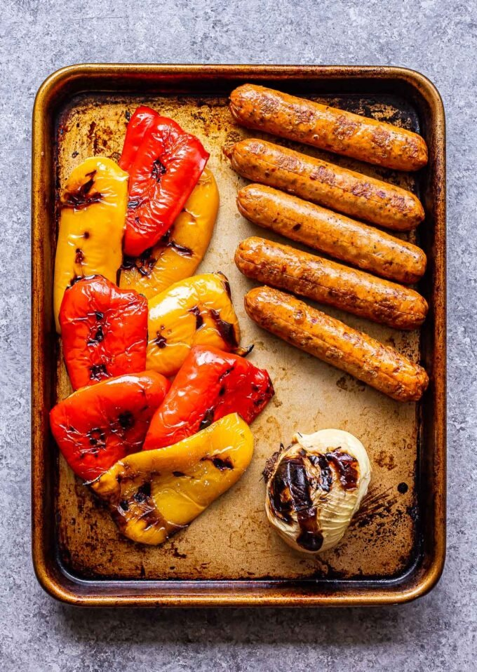 Grilled Sausage, Peppers, and onion on a sheet pan.