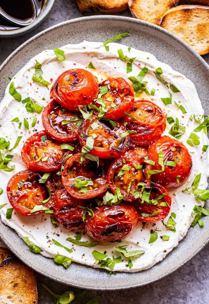 ricotta spread onto a gray plate and topped with grilled tomatoes. Garnished with chopped herbs and balsamic glaze.