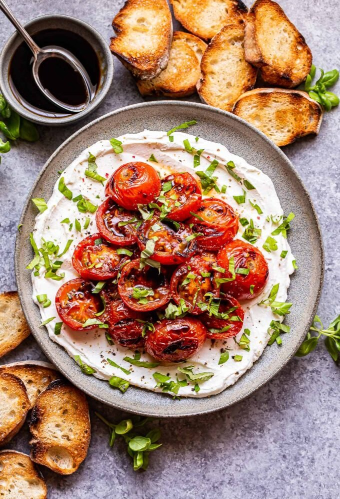 Grilled Tomatoes with Ricotta topped with fresh herbs and balsamic glaze on a gray plate. Slices of baguette next to the plate and a bowl of balsamic glaze behind it.