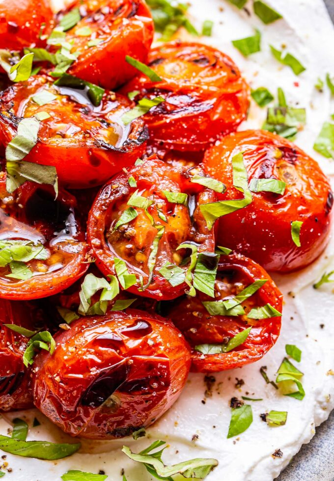 Grilled Tomatoes cut in half on top of Ricotta and sprinkled with fresh herbs and balsamic glaze