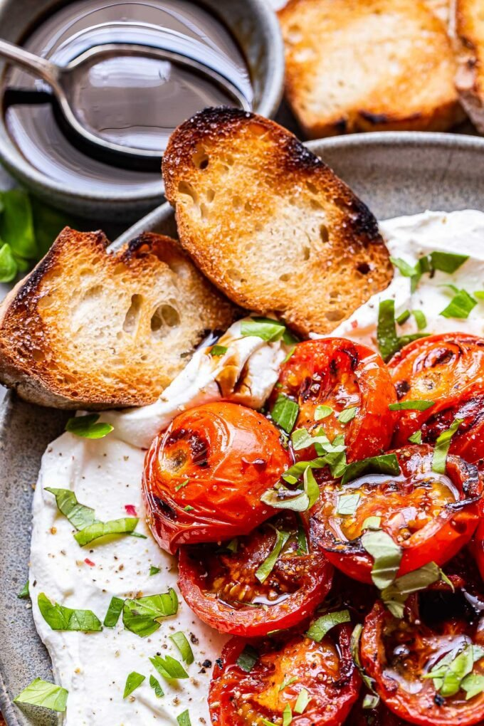 Grilled Tomatoes with Ricotta on a gray plate with two sliced of baguette.