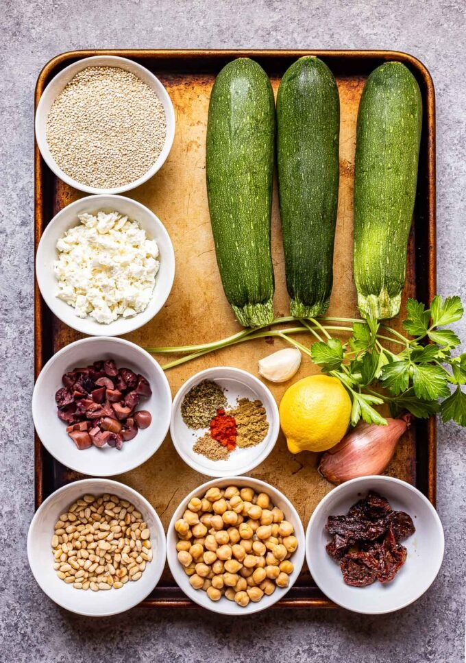 Ingredients used to make Mediterranean Zucchini Boats on a sheet pan.