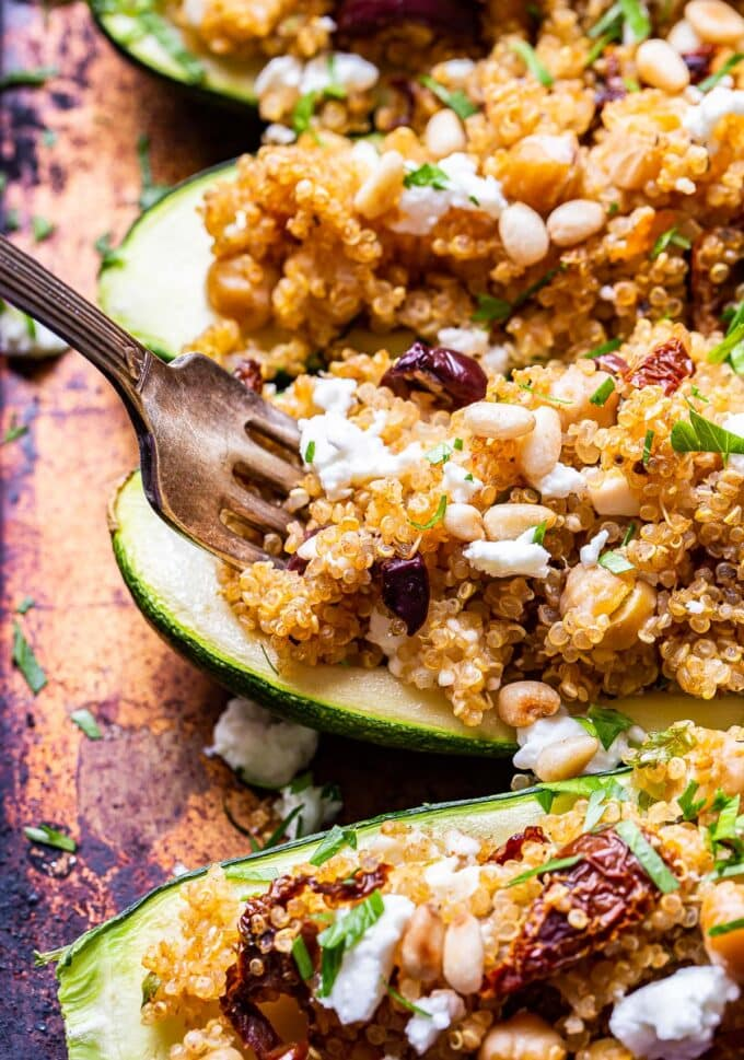 fork scooping up the quinoa filling from one of the Mediterranean Zucchini Boats