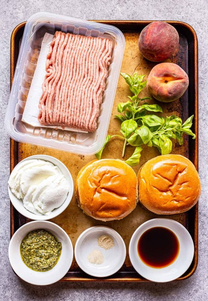 ingredients used to make Peach Caprese Burgers on a sheet pan.