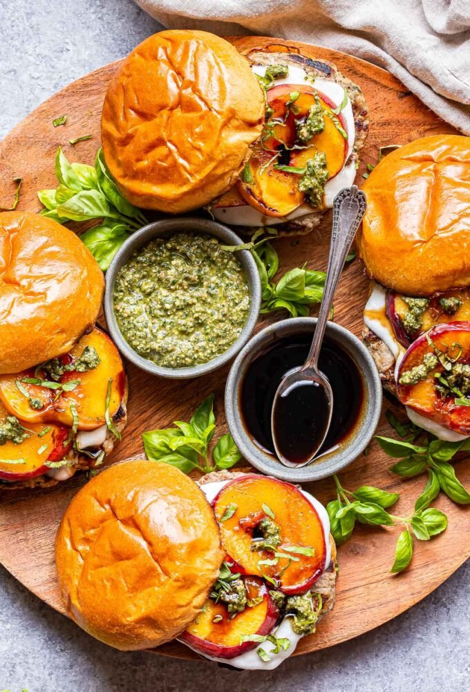 4 Peach Caprese Burgers on a round wooden platter with a bowl of pesto and a bowl of balsamic glaze in the middle.