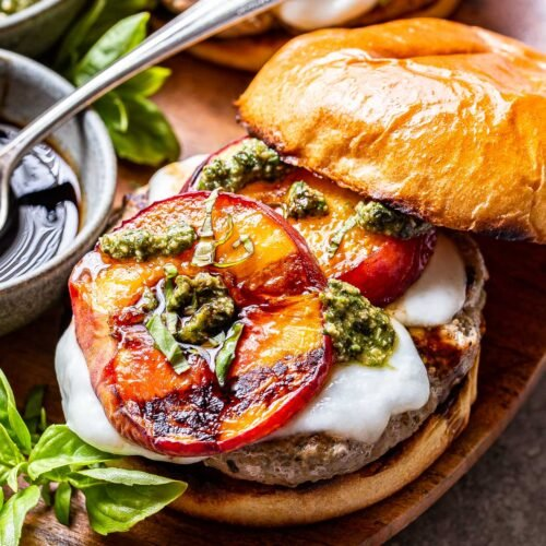 Peach Caprese Burger topped with fresh mozzarella, grilled peach slices, pesto and balsamic glaze. The top of the bun is halfway off the burger.