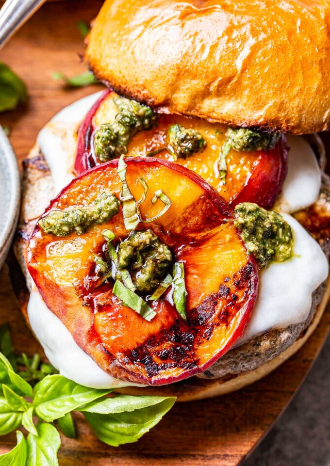 closeup photo of Peach Caprese Burger topped with melted mozzarella, grilled peaches, pesto and balsamic glaze.