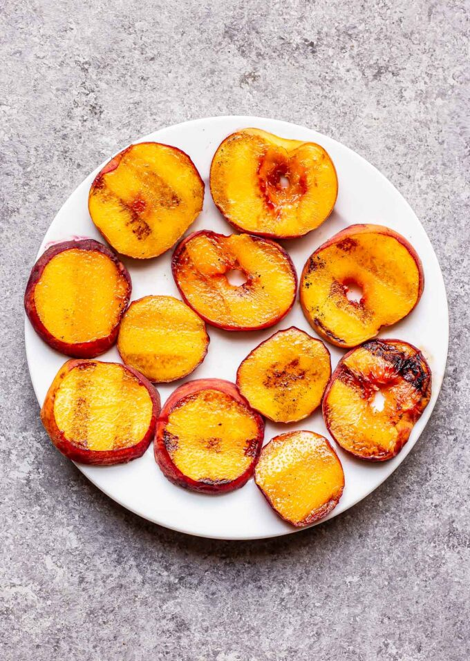 Grilled peach slices on a white plate.