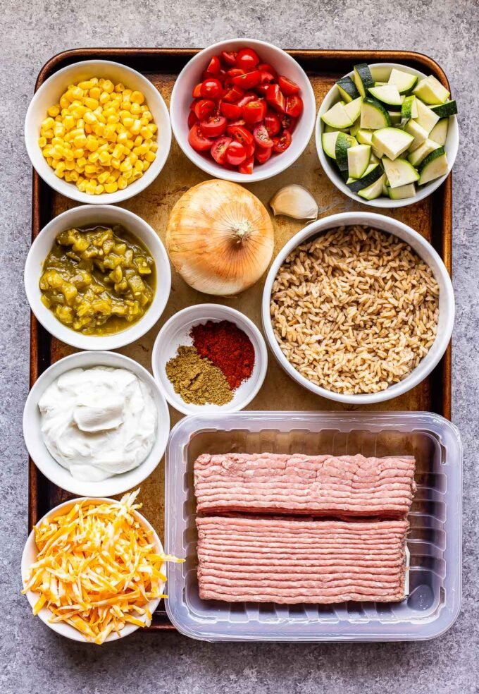 Ingredients used to make Southwest Turkey Vegetable and Rice Skillet on a sheet pan.