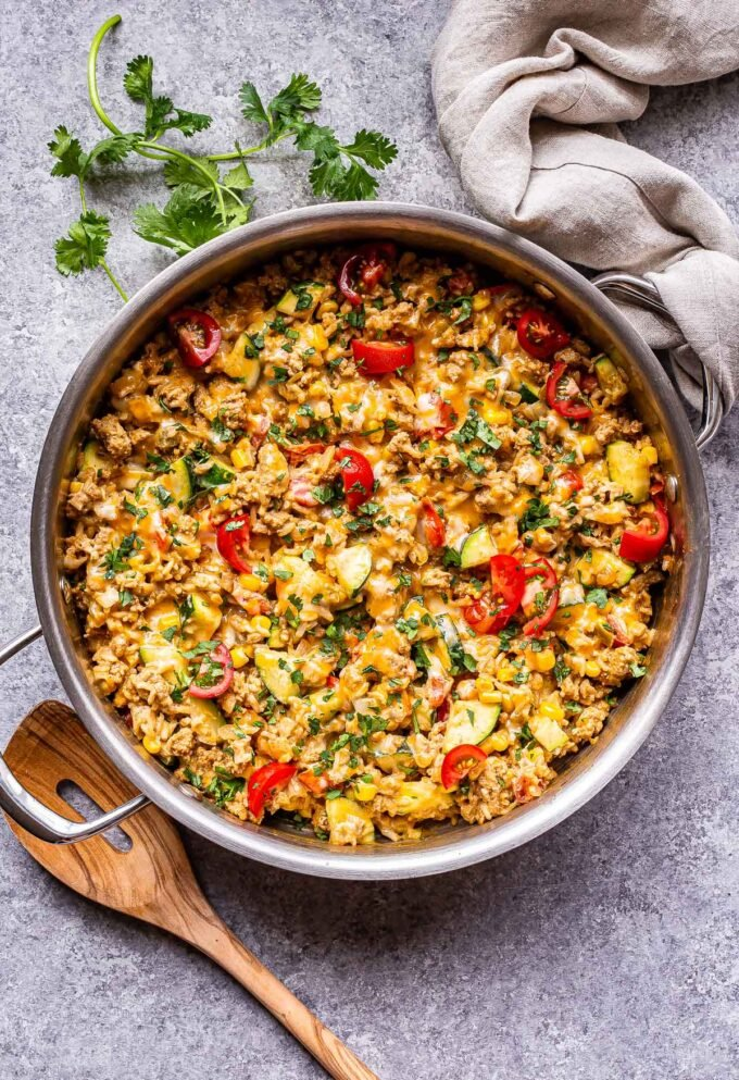 Southwest Turkey Vegetable and Rice with tomatoes, zucchini and corn in a skillet with a wooden serving spoon next to it and a dish towel around the handle.