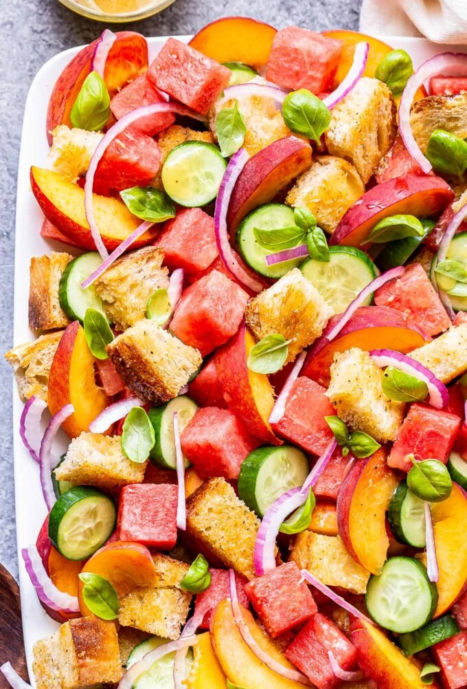 Watermelon Peach Panzanella Salad with cucumbers, red onion and basil on a white serving platter.