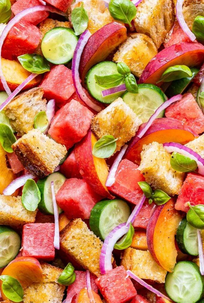 Closeup photo of Watermelon Peach Panzanella Salad with cucumbers and basil.