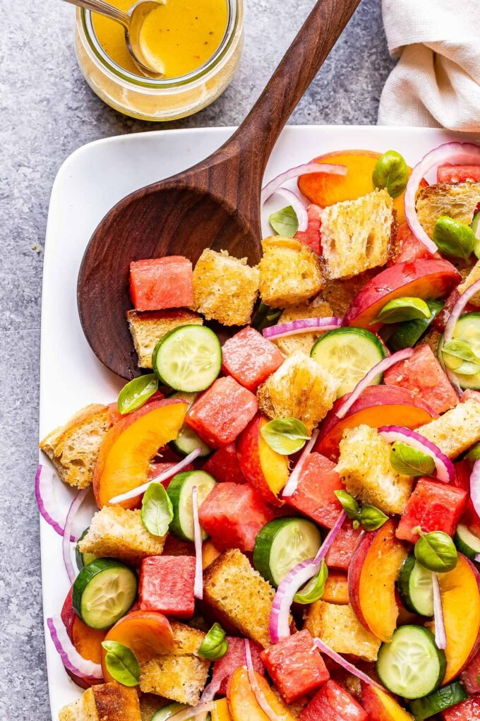 Watermelon Peach Panzanella Salad on a white serving plate with a wooden spoon on the plate.