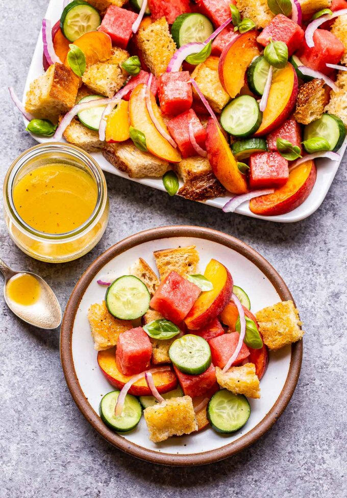 Watermelon Peach Panzanella Salad on a white serving plate with a small plate of the salad in front and a jar of the vinaigrette behind the plate.