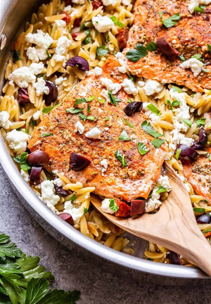 wooden spoon holding up a salon fillet on top of greek orzo.