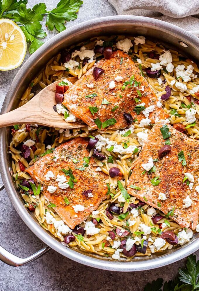 Greek Salmon and Orzo in a skillet with a wooden spoon lifting up one of the salmon fillets.